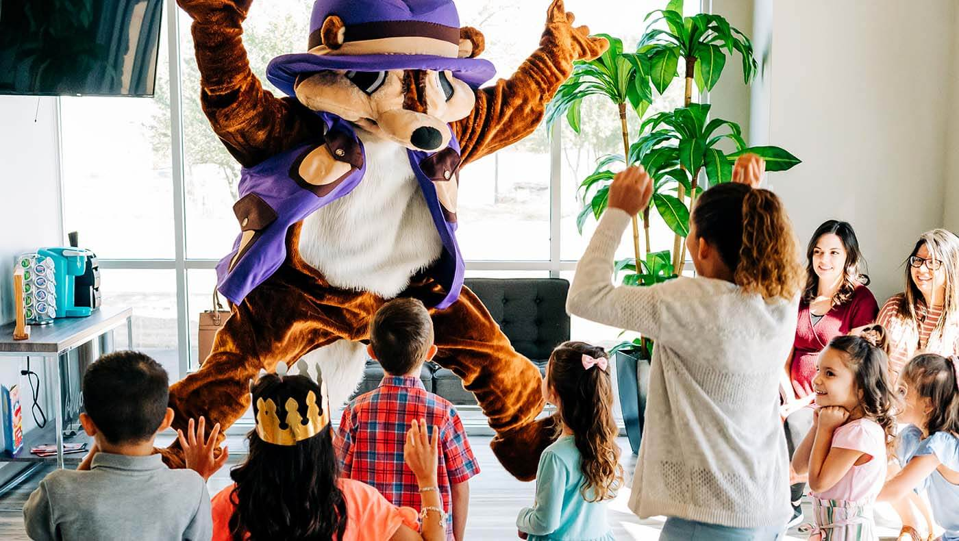 An office mascot jumps and plays with a group of pediatric patients, creating a positive dental office culture for patients.