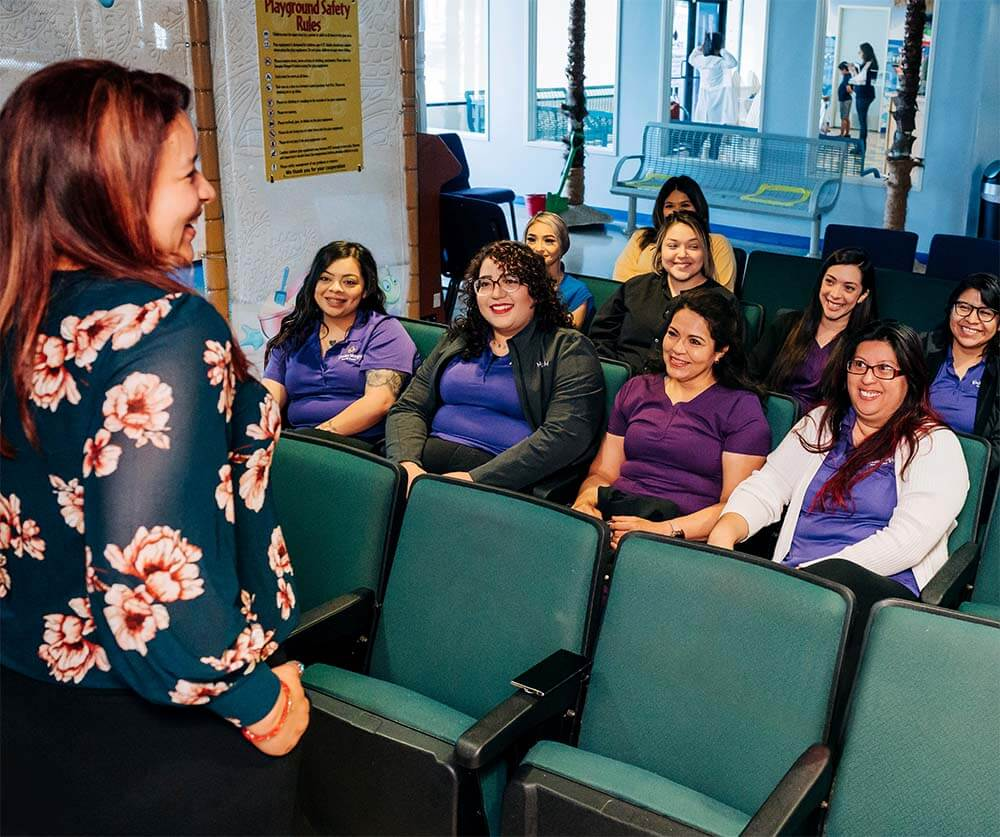 A practice leader meets with her team, fostering a positive dental office environment.